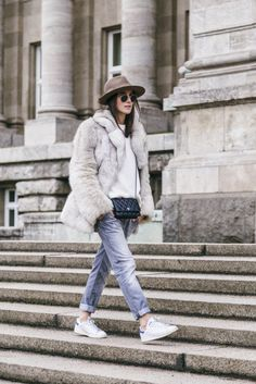A big faux fur coat will add instant glamour to any look. Lena Lademann wears this classic white fur over a knit sweater and boyfriend jeans, an edgy every day look which is ideal for the winter season. Brands not specified.