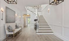 The two-story entrance hall features a sweeping staircase leading upstairs to the property's six bedrooms
