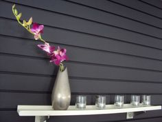 Black accent wall using slatwall... I would spray paint it pink or purple and use the acrylic shelves