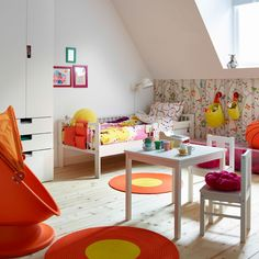 A colourful children's room with a white bed made with colourful quilt cover and pillowcase. Shown with pink rugs, a children's swivel armchair with hood and a white table with two chairs.