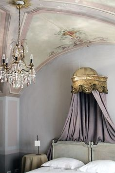 a stunning vault french bedroom with painted ceiling and chandelier
