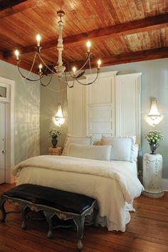 Painted antique doors provide an interesting headboard in the master bedroom, with antique European linens dressing the bed; a pair of painted white pedestals adorned with garlands serves as end tables under the French crystal sconces, while an oversize Julie Neill Designs chandelier of wood and iron with touches of gilt hangs from the exposed pine ceilings.