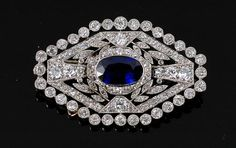 An Art Deco blue sapphire and diamond plaque brooch, the open rectangular shaped platinum brooch collet set to the centre with an oval 1.52cts sapphire, surrounded by twenty grain set old cut diamonds weighing 0.30cts, having four diamond set cross bars linked with leaves totalling 0.68cts, the outer frame with thirty two collet set old cut diamonds totalling 0.76cts, all with millegrain finish and set with further diamonds, to a locking pin