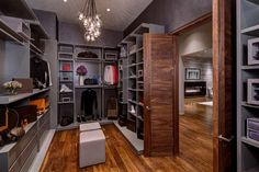 This mostly gray walk-in closet has lots of shelves for displaying shoes and bags.