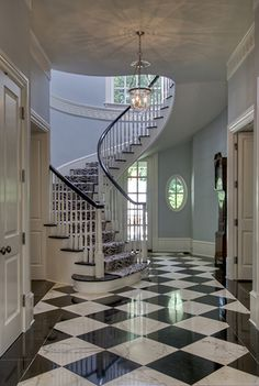 We love the black and white tile that leads up to the stairs in this entryway.
