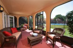 This fully enclosed patio looks out over yard through arched spaces. Red flooring, dark wicker furniture, and stucco wall surfaces complete the look.