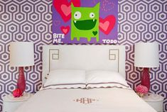 Lara Spencer - Absolutely gorgeous girl's room with art on white and purple hex wallpaper framing white Greek key headboard accented with scalloped shams and monogrammed duvet flanked by pink glass lamps on round lacquered nightstands.