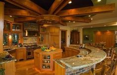 Radial kitchen design with semi-circle two-level island. Wood beamed ceiling in spoke design maintains the radial layout. Extensive use of wood throughout