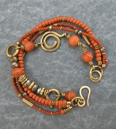 Rust Jasper Multi Strand Bracelet, Boho Beaded Bracelet with Brass Metal Wire Work and Pyrite Beads, Rustic Earthy Multistrand Bohemian OOAK an earthy colored, beaded multi strand bracelet with beautifully striped rust colored jasper beads, small ceramic beads and tiny Toho seed beads in the same color. The jasper beads are wired on brass, with a section of sparkling faceted pyrite beads and African cast brass rings. Two of the small beads strands are strung with brass elements, one is…