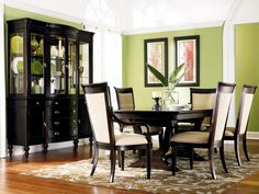A dark wood china cabinet, dining room table and padded chairs contrast beautifully against the soft green walls in this contemporary dining room. Above the picture railing, the walls are painted white to add visual height to the space and to showcase the arch-topped window. A neutral but patterned rug sits over the hardwood floor to anchor the dining table.