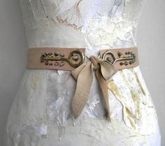 Gold or silver sprayed elastic to hold together, with bow tied over could work for tribal belts. Easier for dancers to get on and off quickly than ties or clips.