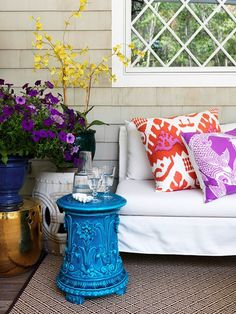 variety of garden stools with potted plants in a corner. Also the koi pillows in bright colors.