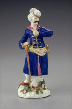 Figure of Turbaned Persian in blue and purple costume; yellow sash, left forearm raised, sword dagger and walking cane, red slippers, flowers in relief on white base. Reinecke models.