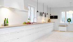 Een witte keuken staat mooi naast een grijze vloer en muur