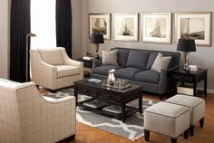 Dark grey couch with comfy chairs.  Love the artwork on the walls.  Would look great with a colorful rug