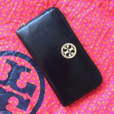 """Tory Burch Zip Continental Wallet Well loved Tory Burch Zip Continental Wallet. Stacked """"T"""" logo at the front, (lightly tarnished) goldtone hardware makes it an ideal everyday wallet. Missing the outside zipper pull, I used a cute tassel keychain instead--be creative! Supple leather inside features a center zip compartment for coins, receipts, etc., 8 credit card slots and 2 billfold sections. Measures approximately 7.5"""" by 4.5"""" by 1"""" See photos for signs of wear, no rips or deep…"""