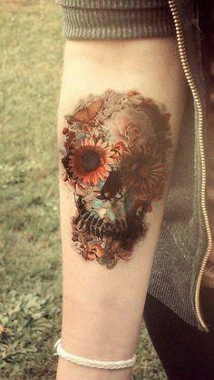 Skull made of flowers forearm tattoo