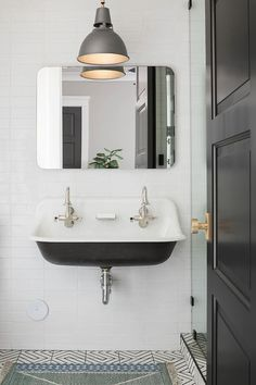 A gray industrial light pendant lights a Restoration Hardware Bristol Flat Mirror fixed on white stacked backsplash tiles above a Kohler Brockway Sink finished with stain nickel vintage faucets and positioned over a blue bath rug placed on black and white floor tiles.