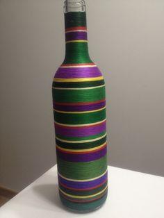 Botella decorado con hilos en tonos verdes y violetas