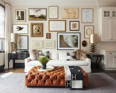 An eclectic art gallery stands over a white skirted sofa lined with black and gray pillows flanked by mismatched black end tables and metal artichoke lamps facing a cognac colored leather tufted ottoman as coffee table draped in a black Hermes Avalon Blanket.