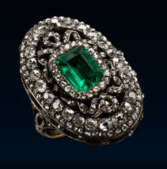 Louis XVI Style Ring, Early 19th Century. Gold and silver ring with a looped diamond ribbon,  bezel outlined by a double row of small and larger old mine brilliant cut diamonds centred on a square emerald in a diamond frame encircled by a ribbon tied with bowknots  above and below.
