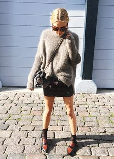 Fuzzy sweater, black mini skirt, and point-toe loafers