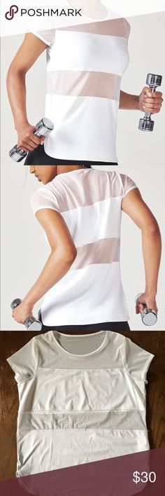 Daniela S/S Top- White This performance tank features moisture-wicking material and all-way stretch technology. The semi-sheer mesh paneling is great for breathability. This top is semi-fitted and tunic length. For women with larger breast, i recommend sizing up so that the mesh panel lays better. I typically wear a large but sized up for that reason. Worn once. Fabletics Tops Tees - Short Sleeve