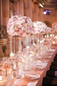 An elegant array of all rose centerpieces drip with crystal adding a glamorous effect to this reception table.