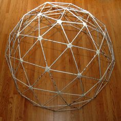 A 5 foot geodesic dome made with newspapers and masking tape. A curved structure with no angles or corners can be made with thin and lightweight materials and be remarkably strong.