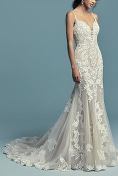 Maggie Sottero - ABBIE MARIE, Embroidered lace motifs and crosshatching dance over the illusion fit-and-flare skirt in this sexy wedding dress.