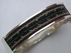 Sterling silver hinged bangle bracelet with 7 braids, 14 kt gold latch pin with ruby.