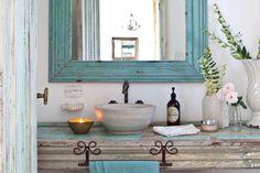 Espejo con marco celeste decapado (Muebles de Antes) coronado por un aplique de hierro en el mismo estilo. Completan una jabonera de chapa ($150, Puerto de Frutos) y un cesto de ratán.  /Santiago Ciuffo