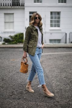 Emma Hill wears khaki utility jacket, black white stripe t-shirt, cropped flare frayed hem jeans, canvas wedge espadrilles, Simon Miller tan suede Bonsai bag, casual Spring outfit