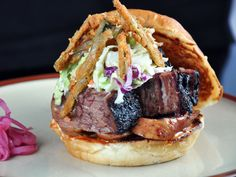 """Char Bar — Kansas City, Mo. : At Char Bar, owner Cory Puckett and Chef Michael Peterson are putting a modern twist on Kansas City barbecue. The Burnt Heaven Sandwich is the perfect example. The cubed burnt ends carved from the fat cap of a smoked brisket get piled high with slices of smoked kielbasa, chipotle mayonnaise, coleslaw and fried jalapenos on a buttery bun. Also worth trying are the Cheesy Hushpuppies made with cheese and jalapenos. They're served with """"beer"""" blanc,..."""