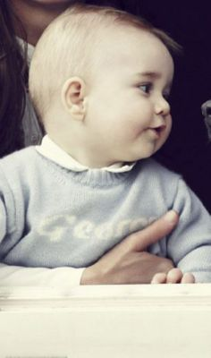 Eight months old Prince George has inherited his father's blonde locks and his mother's dark 'Middleton eyes'. The little prince was wearing a baby blue cashmere jumper with his name embroidered on.