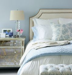 LOVE THE ANTIQUE MIRRORED NIGHTSTAND. Chic bedroom design with ivory headboard with nailhead trim, antique mirrored nightstand, glass stacked lamp, blue quilt and ivory & blue tufted bench. Mirrored Nightstand, Mirrored Furniture, Bedside Dresser, Mirrored Table, Bedside Lamp, Unique Nightstands, Bedside Cabinet, Unique Furniture, Moroccan Decor