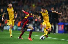 Koke of Club Atletico de Madrid takes on Marc Bartra of Barcelona during the UEFA Champions League Quarter Final first leg match between FC Barcelona and Club Atletico de Madrid at Camp Nou on April 1, 2014 in Barcelona, Catalonia.