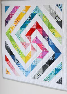 Really cool quilt pattern in colour wheel colors on white. Muy bonita colcha en colores del arco iris sobre fondo blanco.