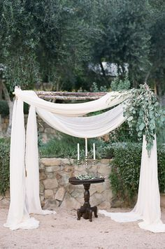 Green leaves accent a wooden arbor draped with cream fabric to create a backdrop fit for a fairytale. Altar, Wedding Decorations, Chuppas, Flowers