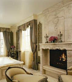 Luxurious and ornate, carved marble master bathroom, complete with fireplace, chaise lounge, and soaking tub