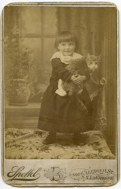 A Young Girl Holding Her Cat But apparently not for long.