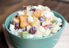A side shot of a bowl of grapes, apples, mandarin oranges, and pineapple as well as marshmallows and coconut, all mixed together with a Greek yogurt dressing.