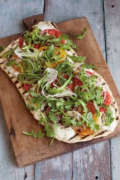 Summer Vegetable Grilled Pizza Recipe   With grilled onions, heirloom tomatoes and peppery arugula mounded on top, this pizza is summer on a plate.
