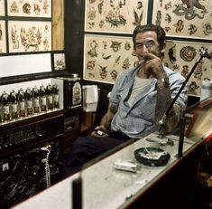 Tattoo-Jim sitting in his Århus shop, regarded as Denmark's most beautiful tattoo parlor at the time. He claimed to be able to remove tattoos and traveled around doing just that, always skipping town before customers realized it's utterly bogus.