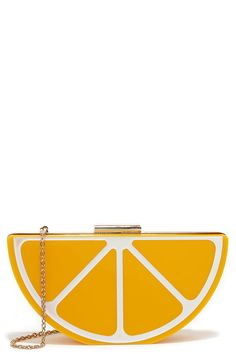 """When it comes to dressing up an outfit, the Pucker Up Yellow Lemon Clutch will be your main squeeze! This adorable plastic clutch has an ultra structured look and lemon wedge design complete with shiny gold accents, hinged bottom, and top latch. The sleek interior offers plenty of space for your lip gloss and phone. Carry as a clutch, or attach the 48"""" long gold chain strap. Clutch measures 9"""" wide, 4.5"""" tall, and 2.75"""" deep. Man made materials."""