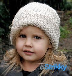 Оригинальная маленькая шапочка от дизайнера Heidi May, на манер капора, только без завязок. Шапочка выполнена с асимметричным отворотом, отделана крупными пуговицами. Фасон, в общем-то, вполне взрослый, хотя и предлагается для девочек.
