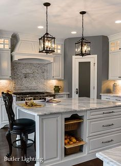 Red Brick Herringbone Cooktop Backsplash with oversized lantern pendants and white cabinets with hood in kitchen