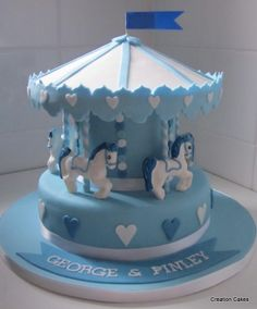 Carousel Cake (two-tier) with handmade hood for twin boys naming ceremony.  http://www.creationcakes.org.uk