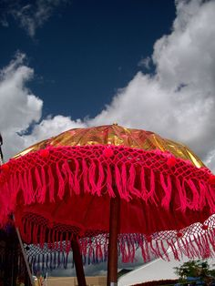 Indian umbrella against a blue sky and billowing clouds.