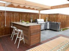 A state of the art grilling area and granite-countertop bar sit underneath a pergola with a retractable canopy.